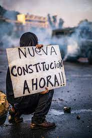 Protestor holding a sign that reads 'nueva constitutión ahora!!!'