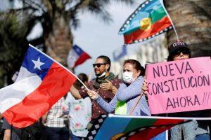 Protestors waving the Chilean flag and holding signs that read 'nueva constitutión ahora!!!'